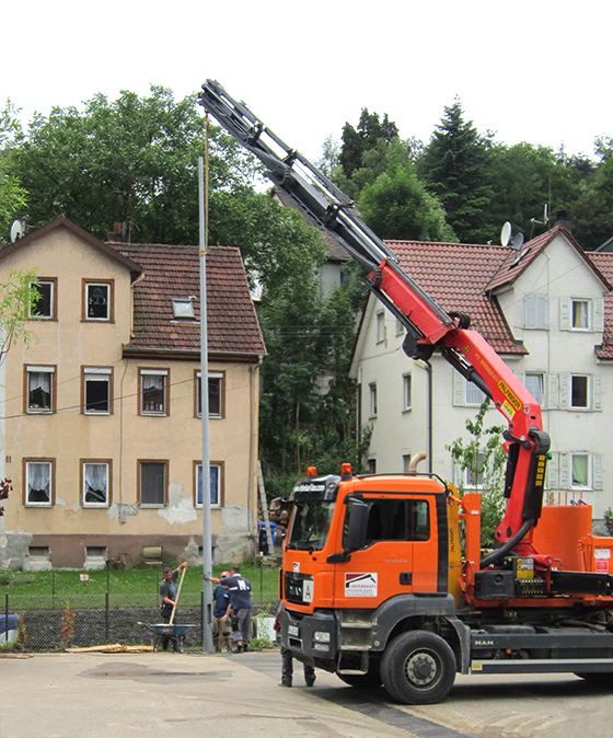 a crane helps mounting the street light
